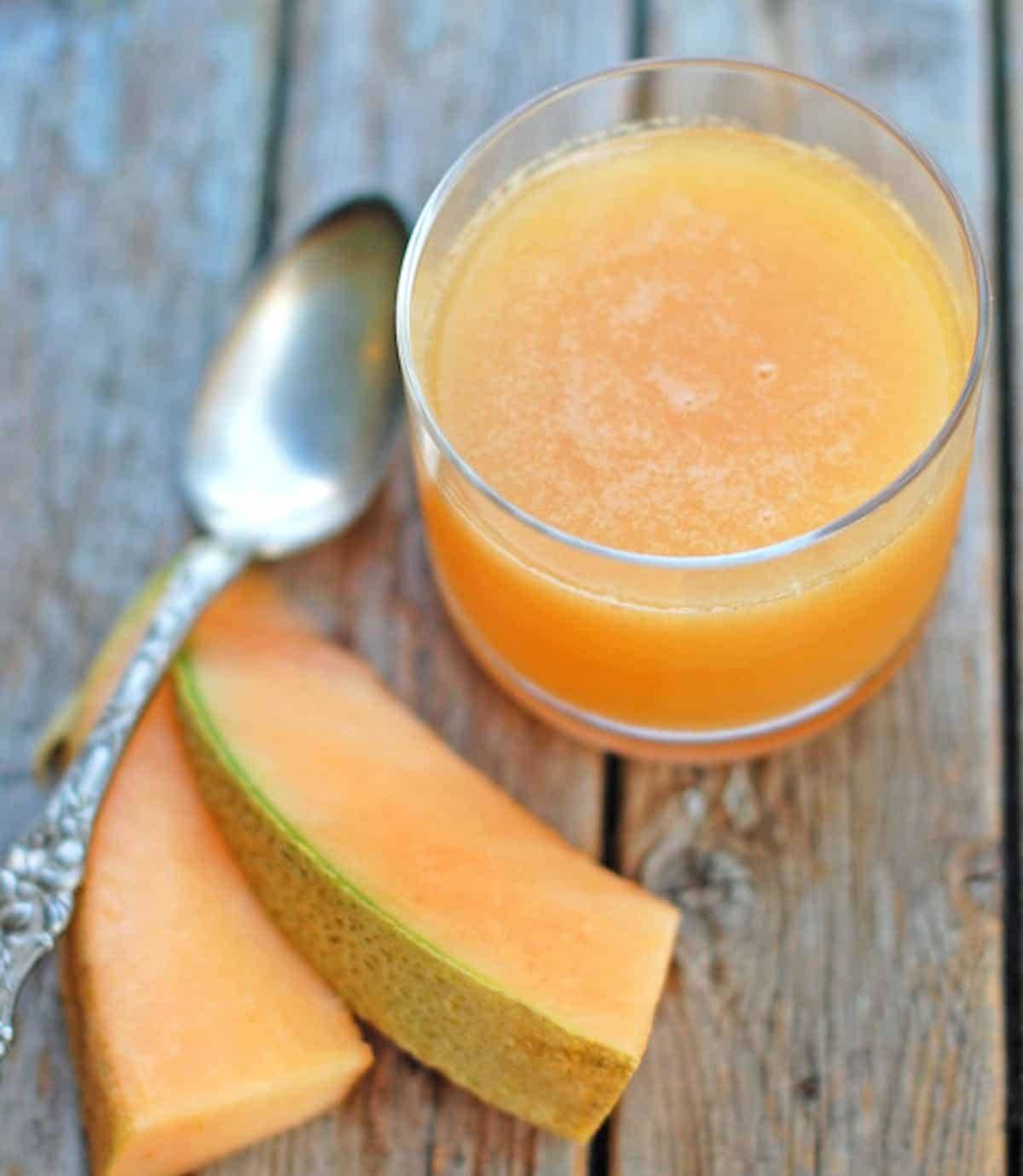 Ginger Melon Chiller in a glass with cantaloupe and a spoon.