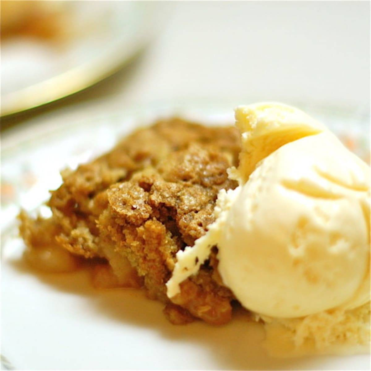 Apple crisp with ice cream on a plate.