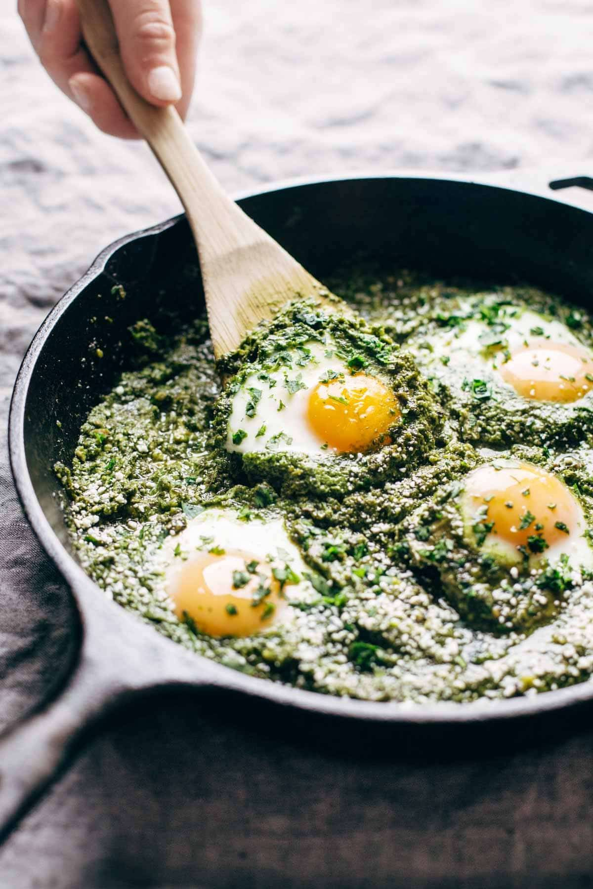 green shakshuka in a pan with a wooden spoon