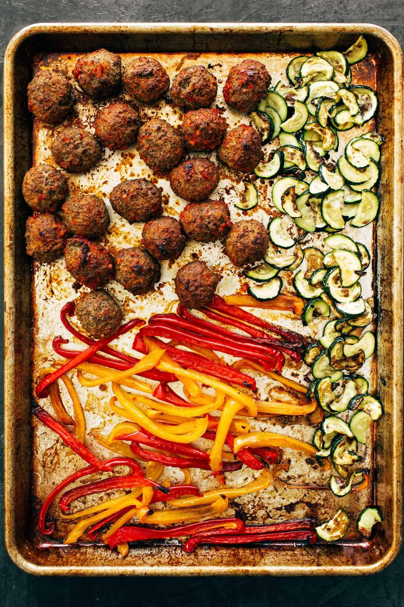 Cooked ingredients on a sheet pan for Harissa Meatballs with Whipped Feta