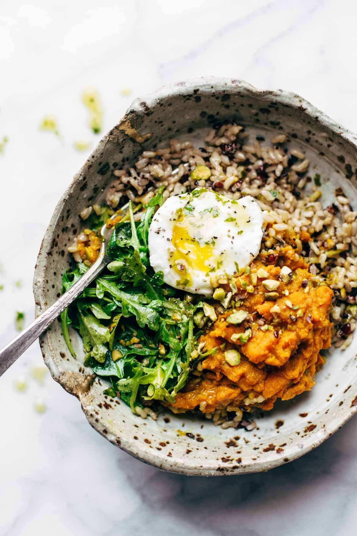 bowl with sweet potatoes and brown rice with an egg and a fork