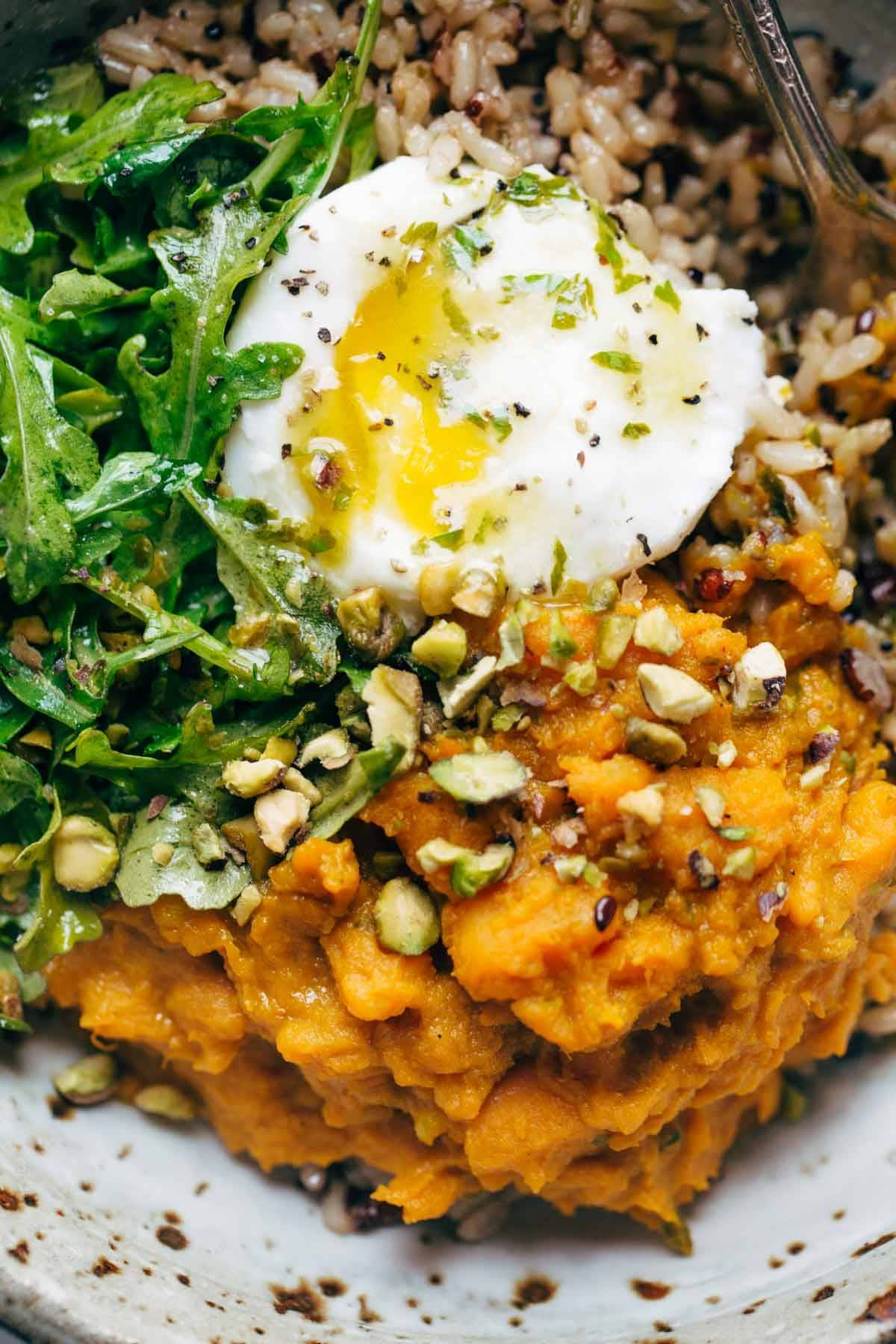 Sweet potatoes with brown rice and an egg in a bowl with a fork.