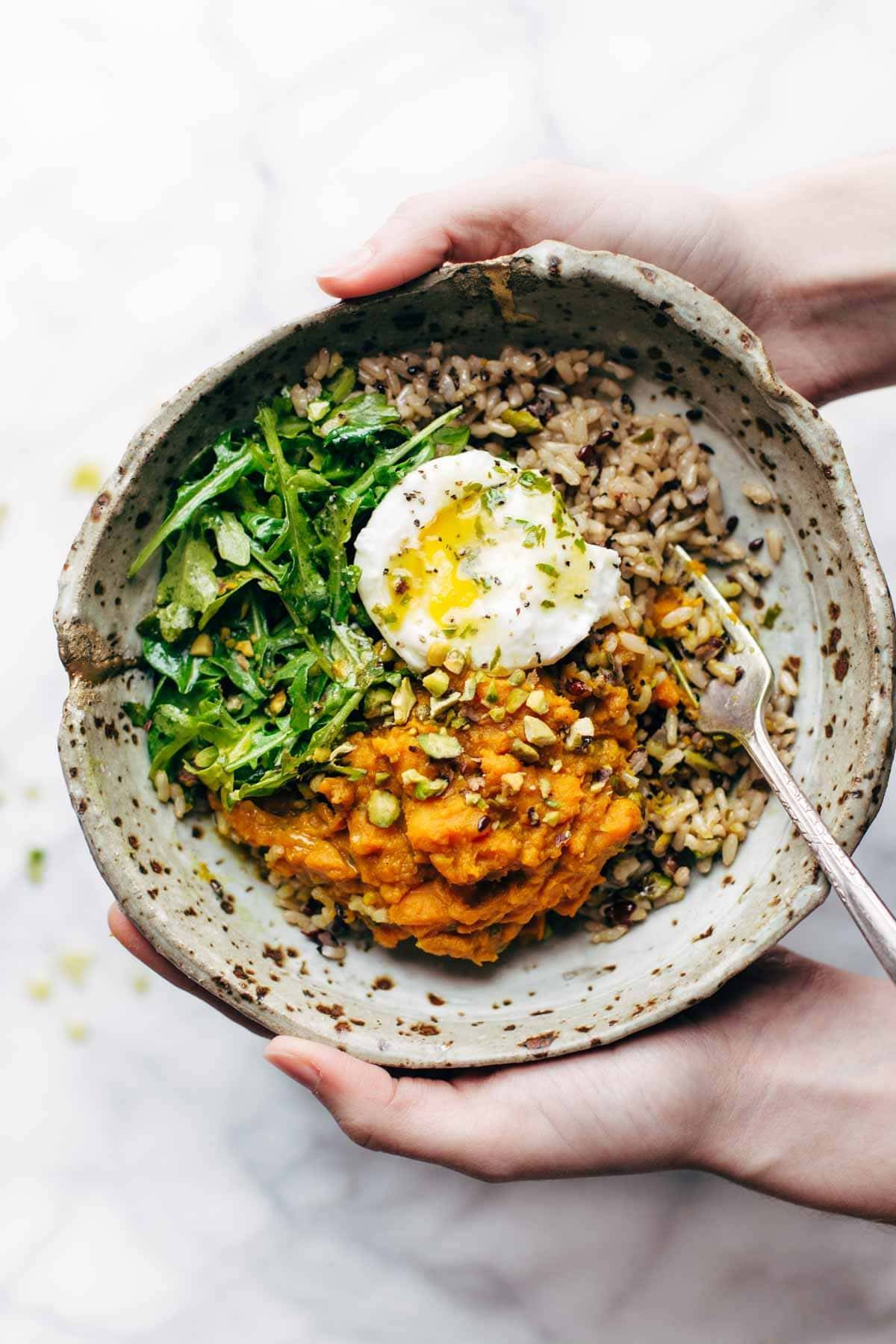 bowl of sweet potatoes and brown rice with an egg and a fork