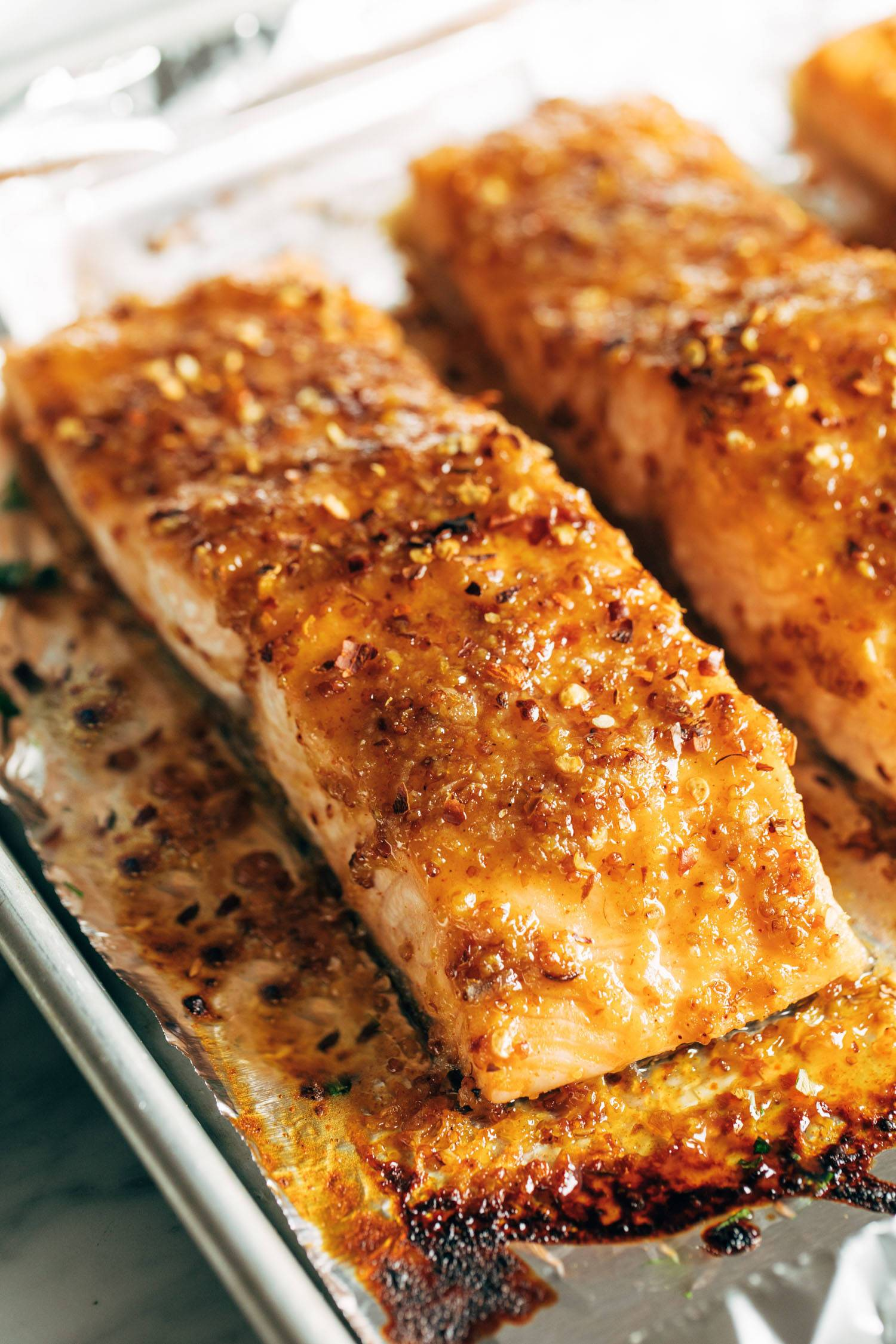 Hot honey salmon on a sheet pan lined with foil.