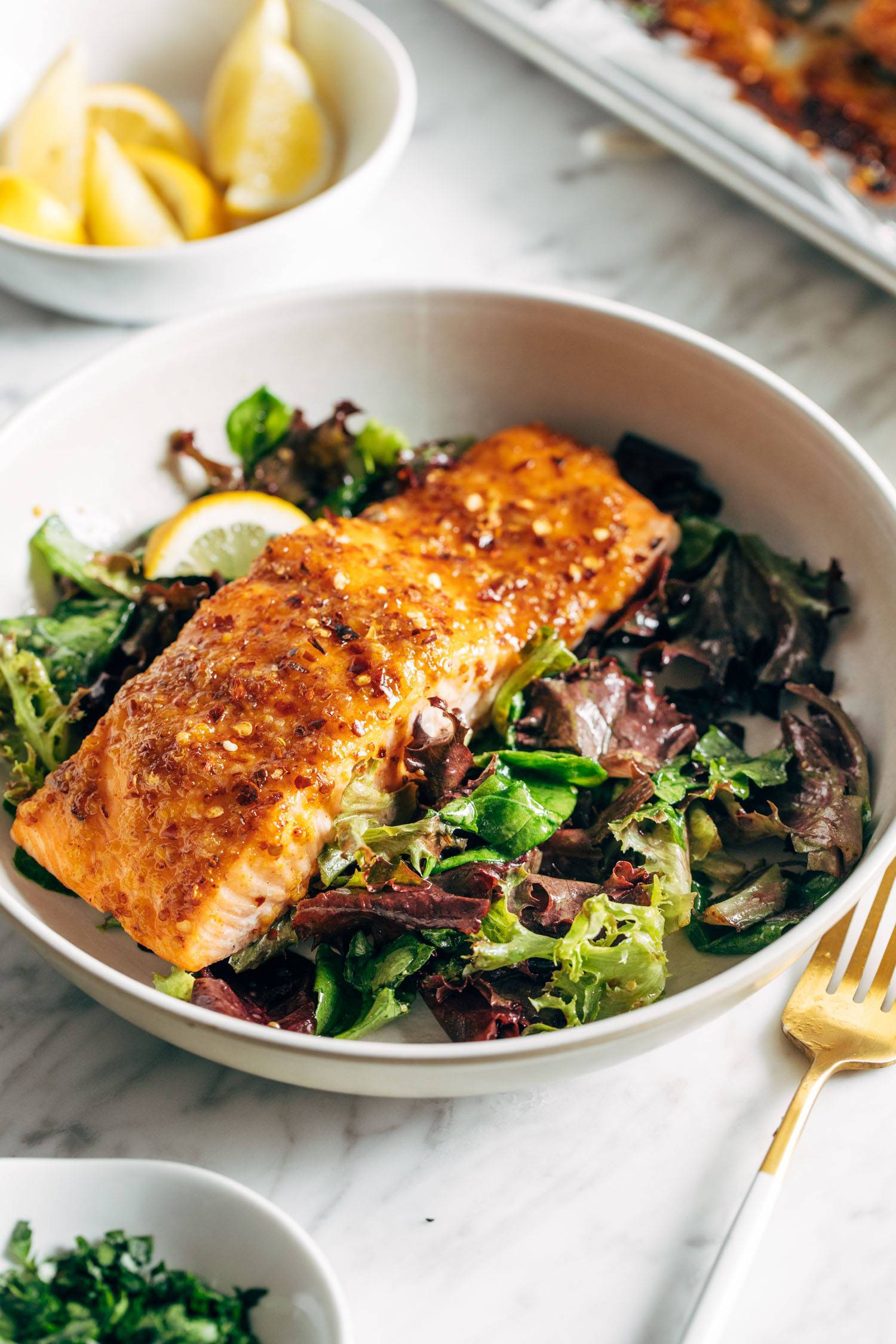 Hot honey salmon in a bowl on top of a green salad. There's a fork on the side of the bowl.