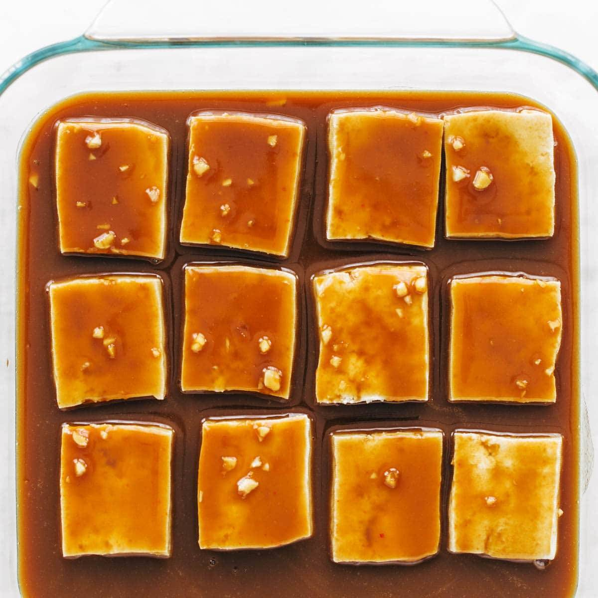 Tofu in baking pan with sauce.
