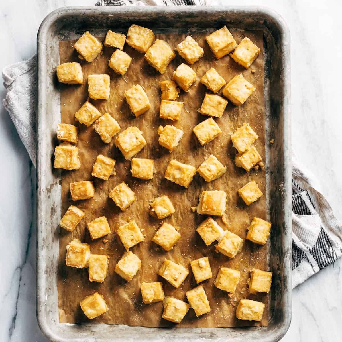Crispy tofu on a baking sheet after baking.
