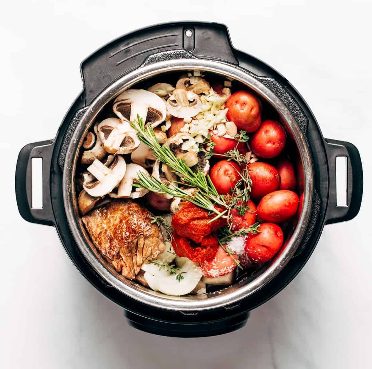 Potatoes, meat, mushrooms, spices, and onions in an instant pot
