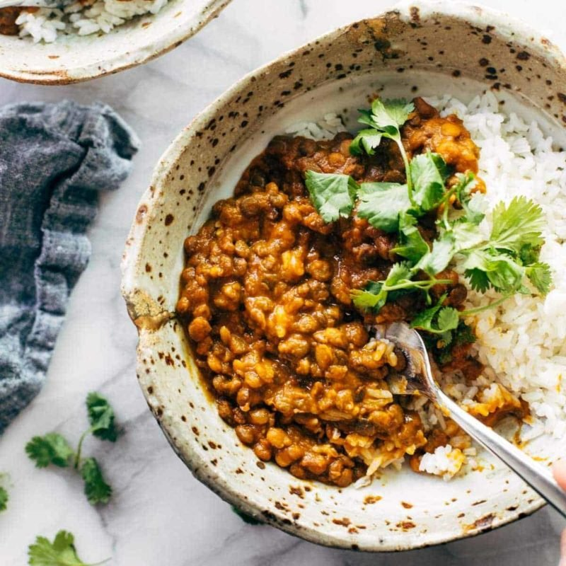 Red curry lentils with rice in a bowl with spoon.