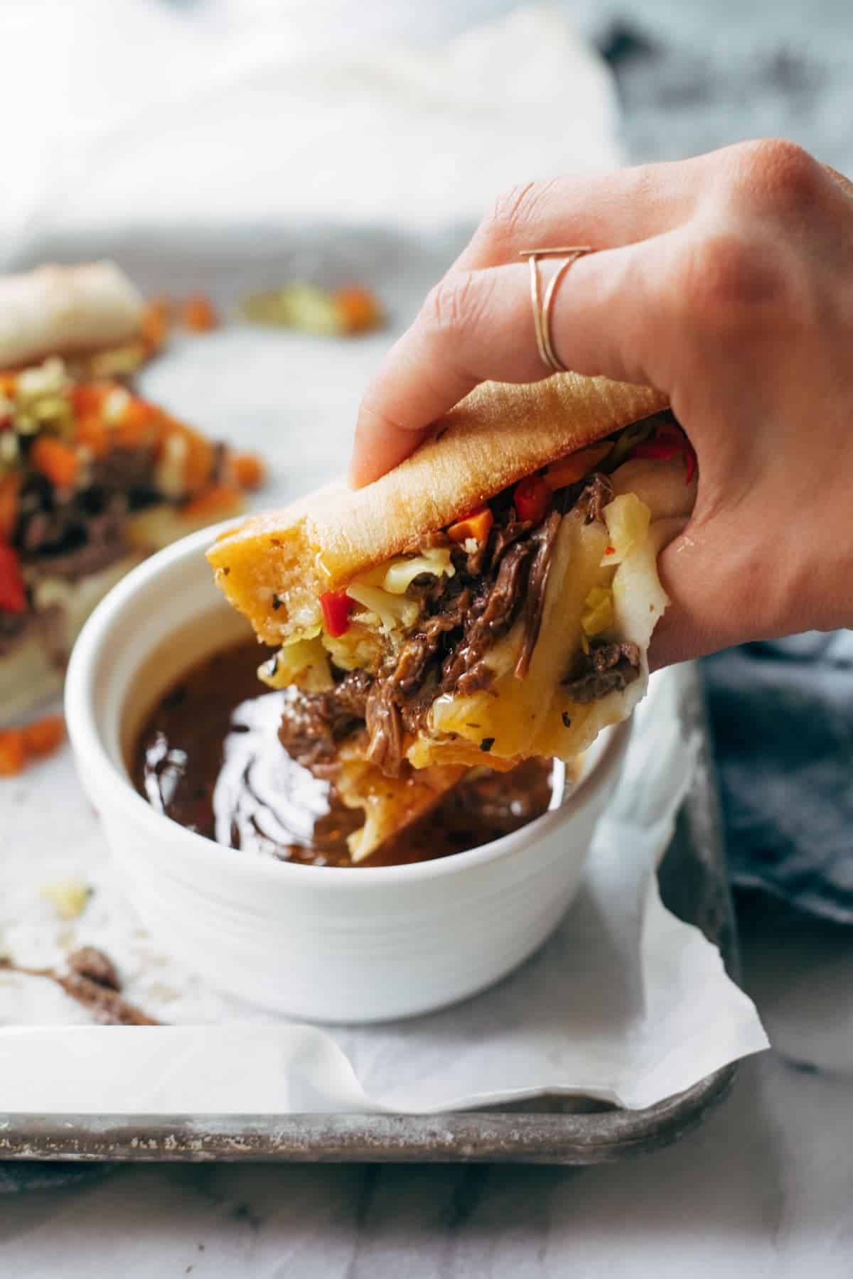 Dipping Italian beef sandwich into sauce.