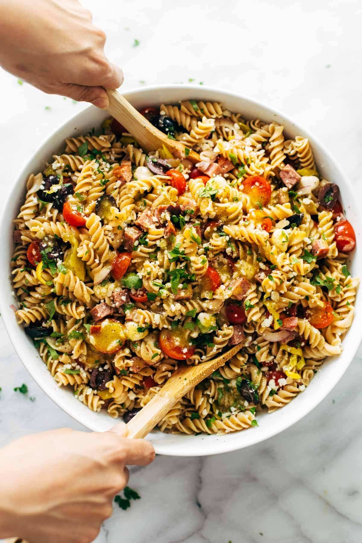 Pasta salad being mixed with spoons.