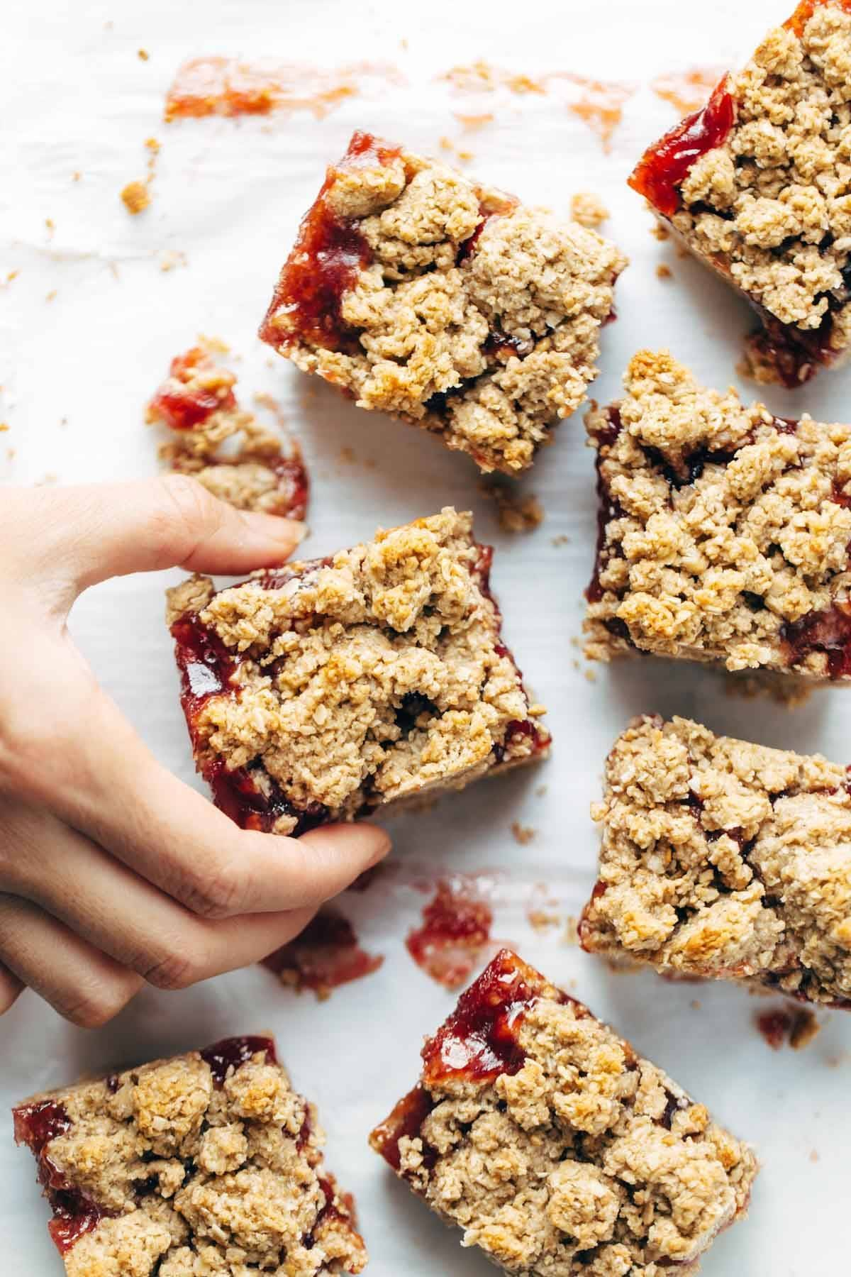 Hand grabbing Strawberry Oat Crumble Bars