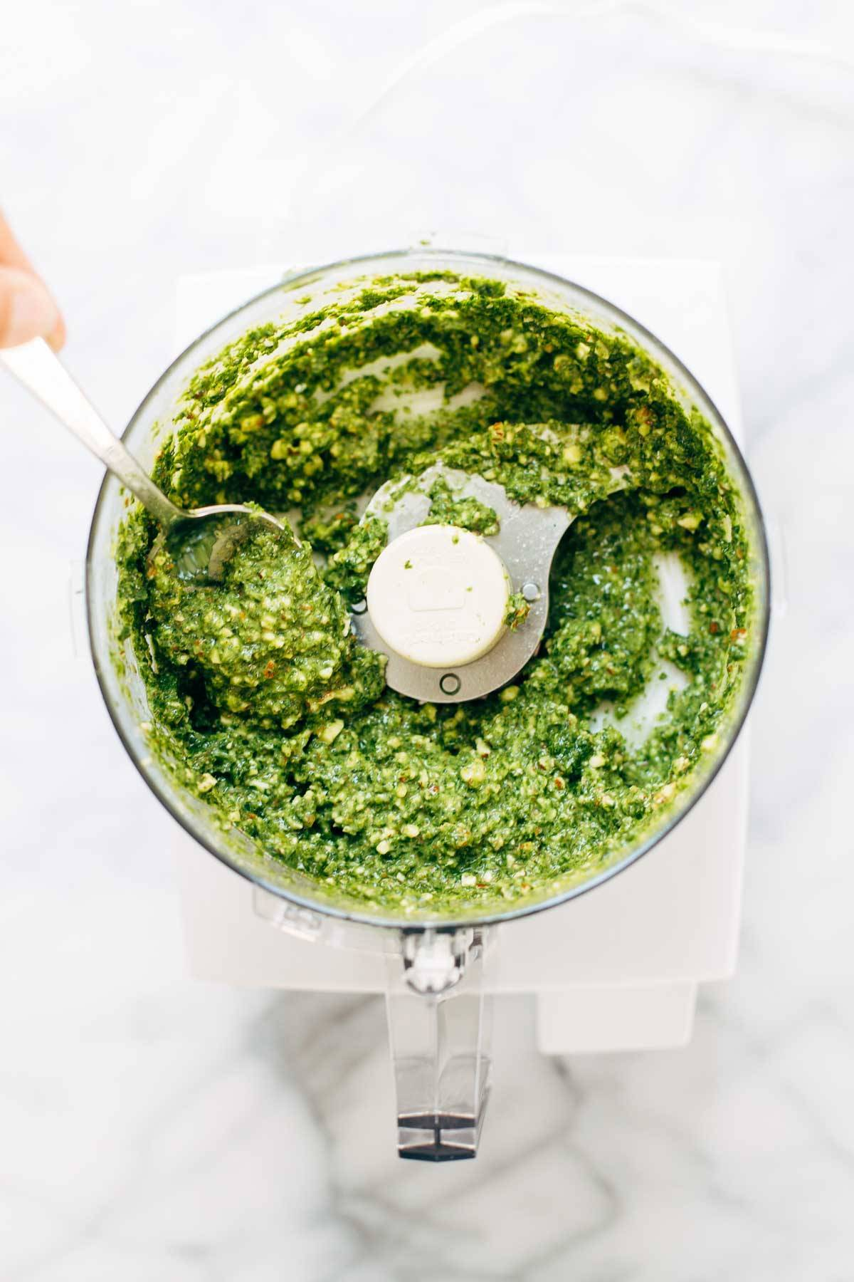 Kale pesto in a food processor with a spoon.