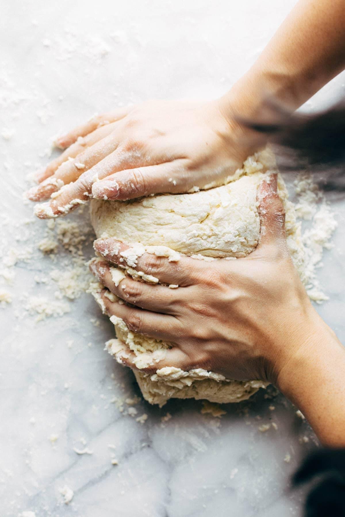 Hands kneading gnocchi dough.