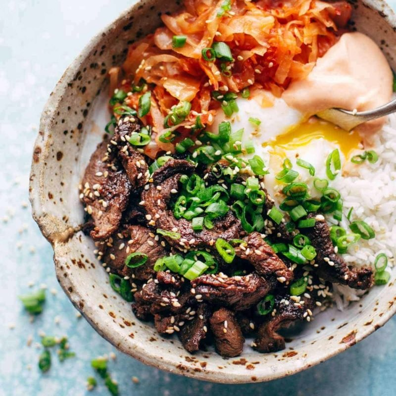 Korean beef along with carrot, onion and spicy mayo in a bowl with a spoon.