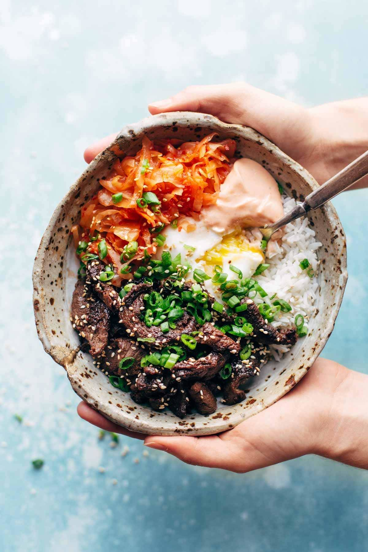 Hands holding a bowl with rice and steak.