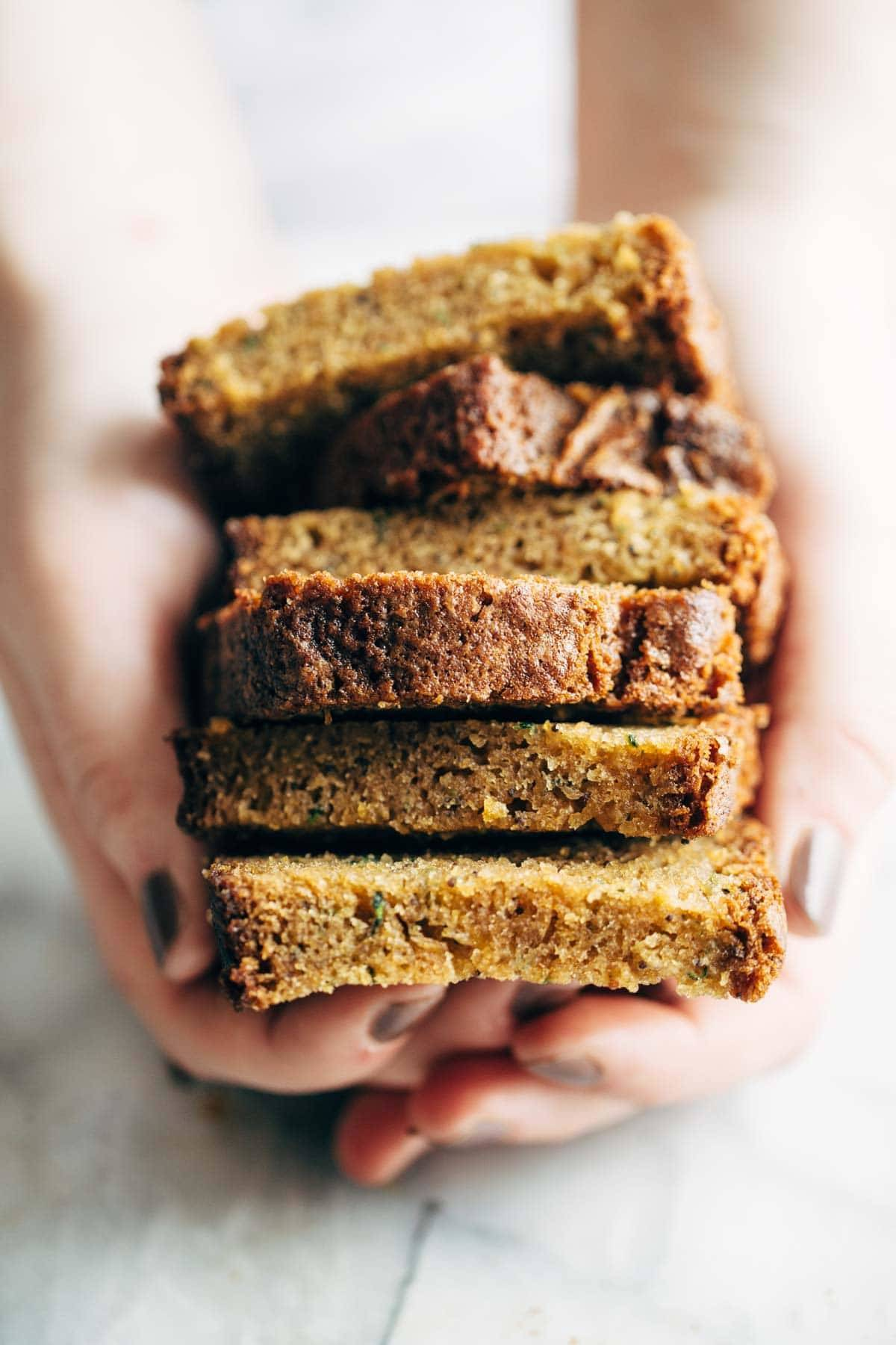 Hands holding lemon olive oil cake.