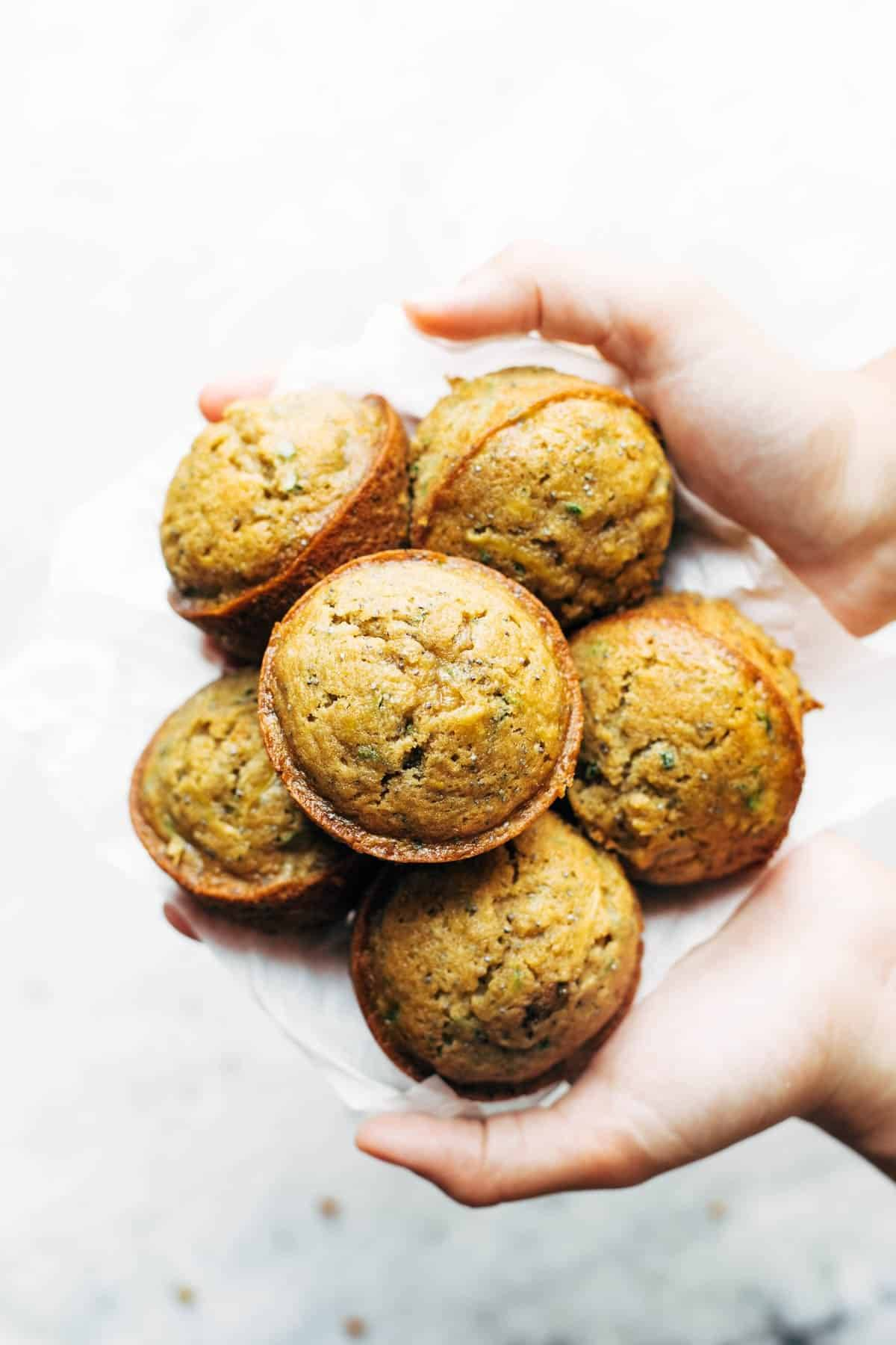 Lemon poppyseed zucchini muffins held by hands.