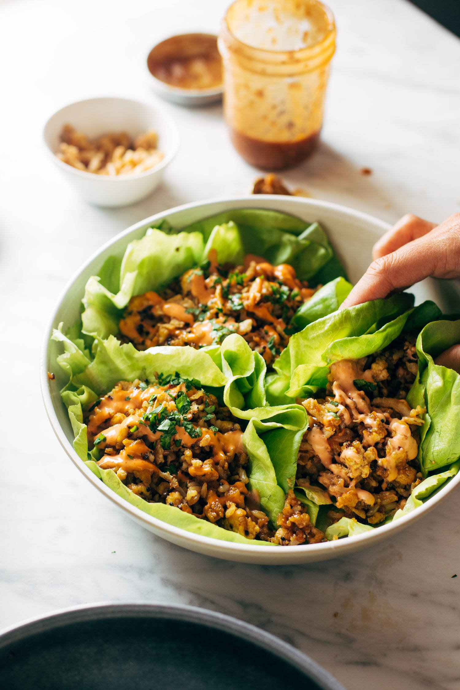 A white hand grabbing a tofu and brown rice lettuce wrap on a platter. There are extra ingredients for the lettuce wraps in the background.