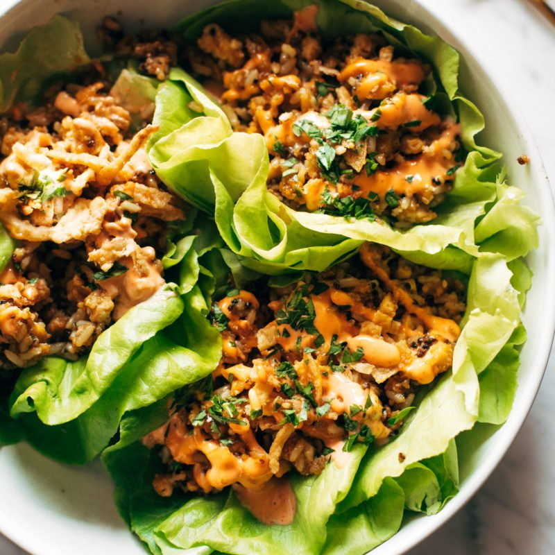 Lettuce wraps on a plate. The wraps are filled with tofu and brown rice and have sauce drizzled on top.