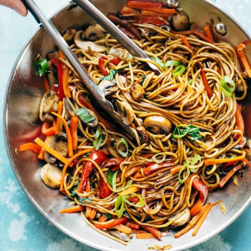 Lo Mein in pan with tongs.