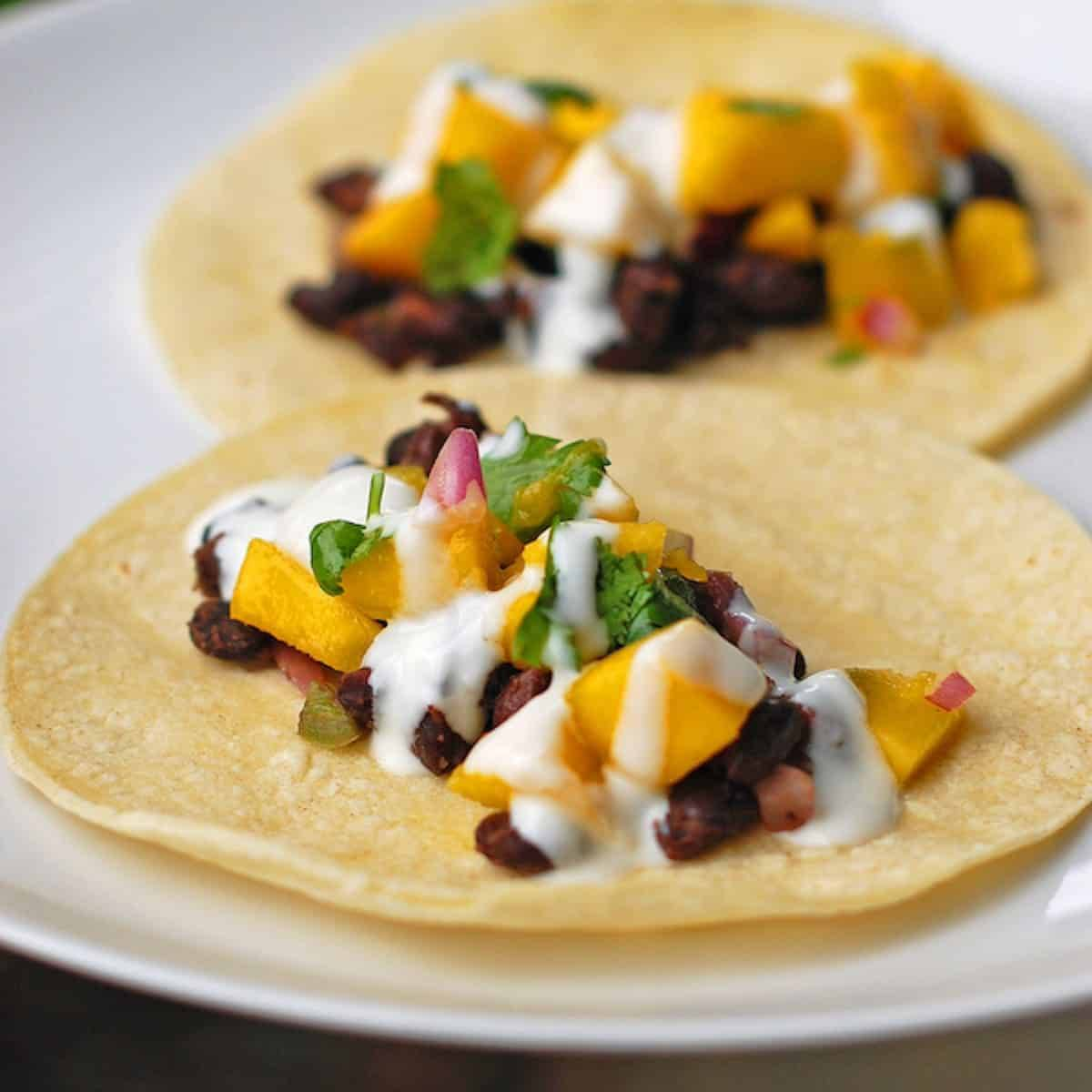These simple, easy, and fresh mango black bean tacos have a deliciously creamy coconut sauce drizzled over the top. So yummy! | pinchofyum.com
