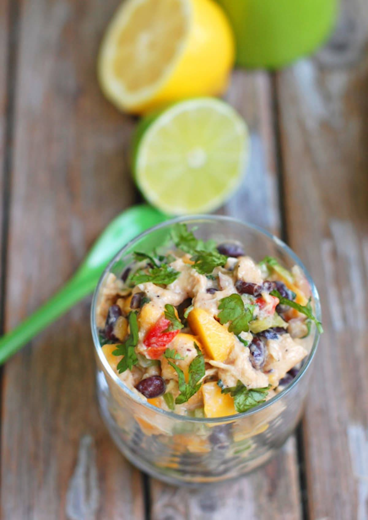 Mango chicken salad in a glass dish with lemons and limes.