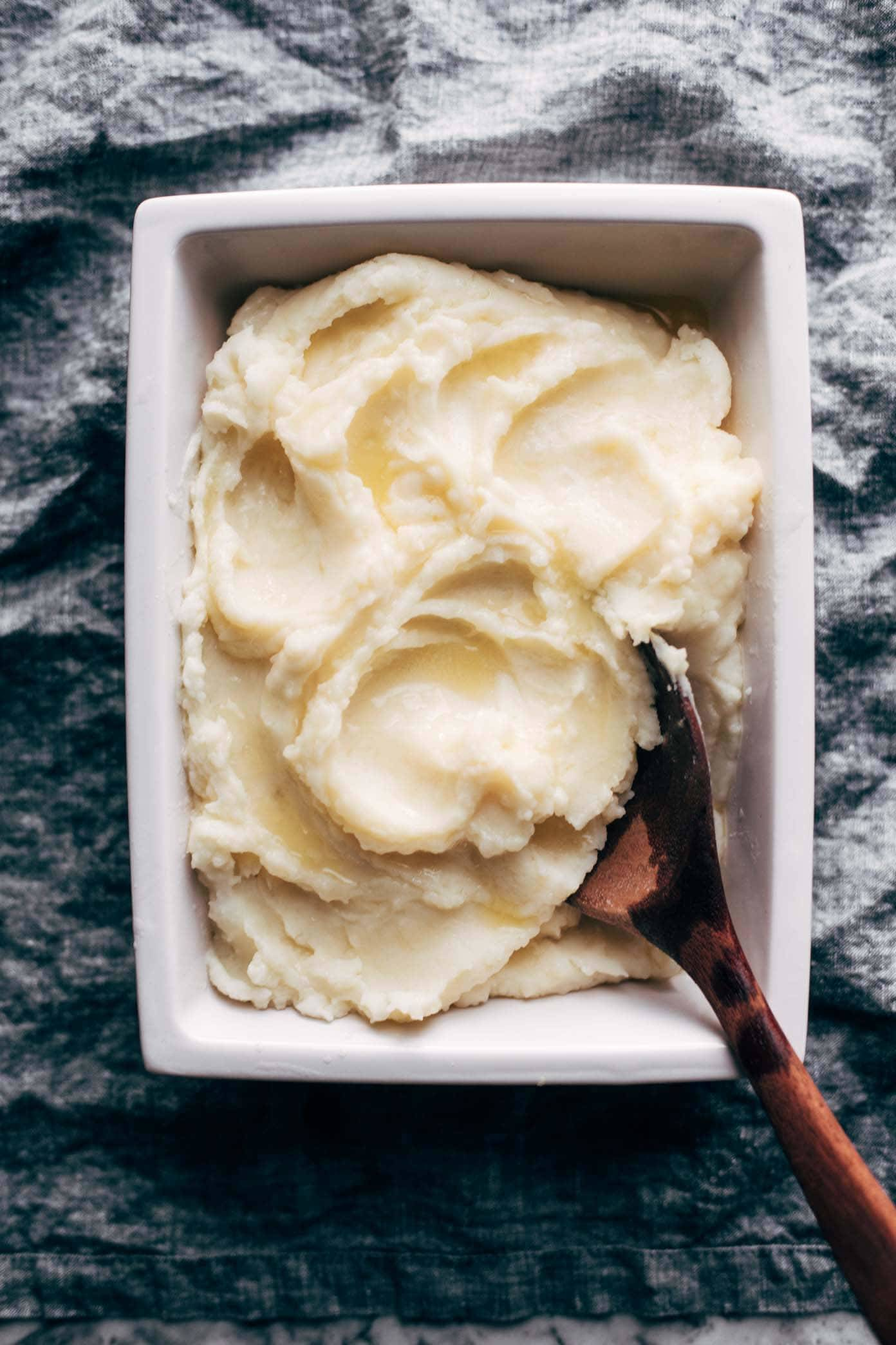Mashed Potatoes in a dish with a wooden spoon.