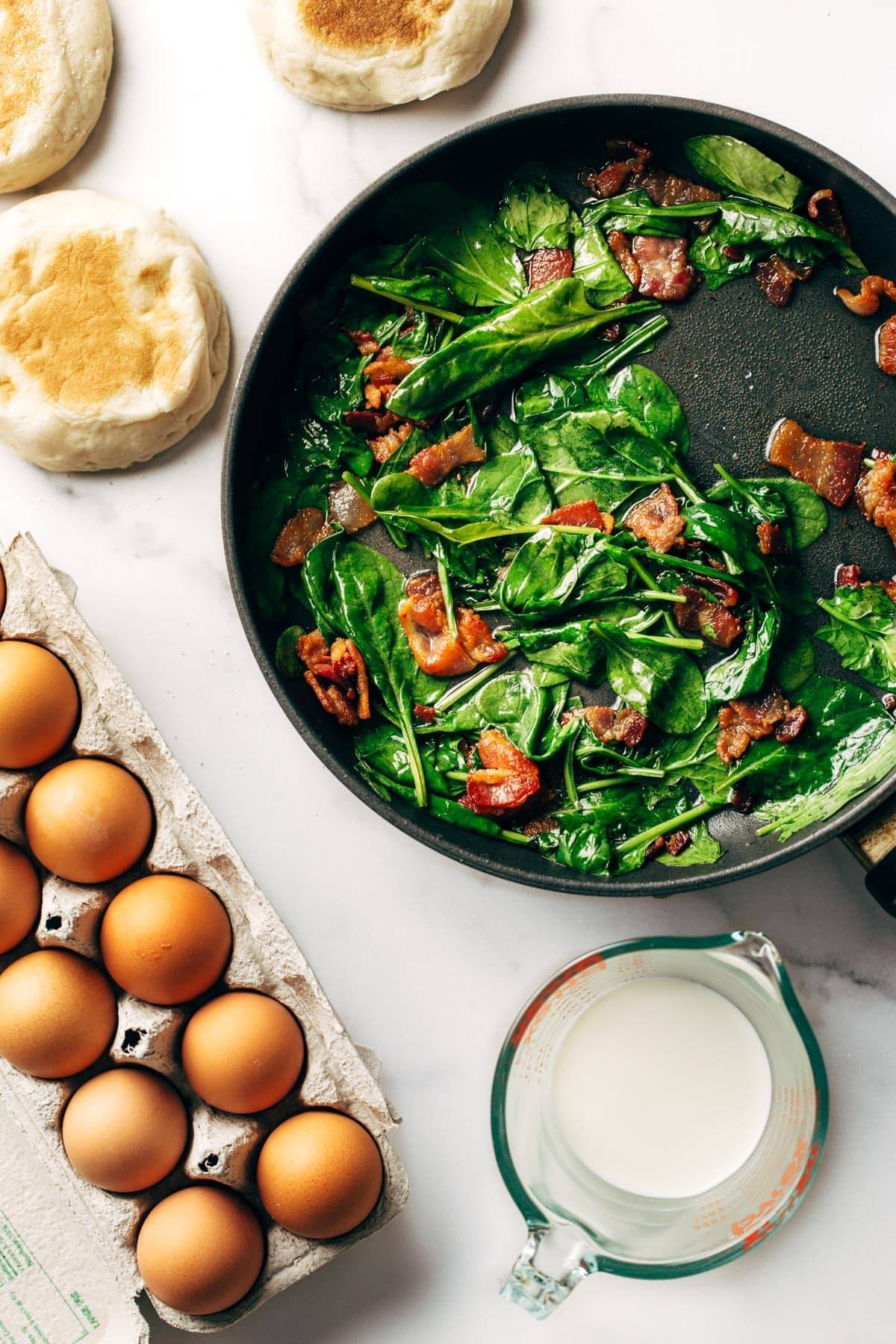 Spinach and bacon in pan with eggs.