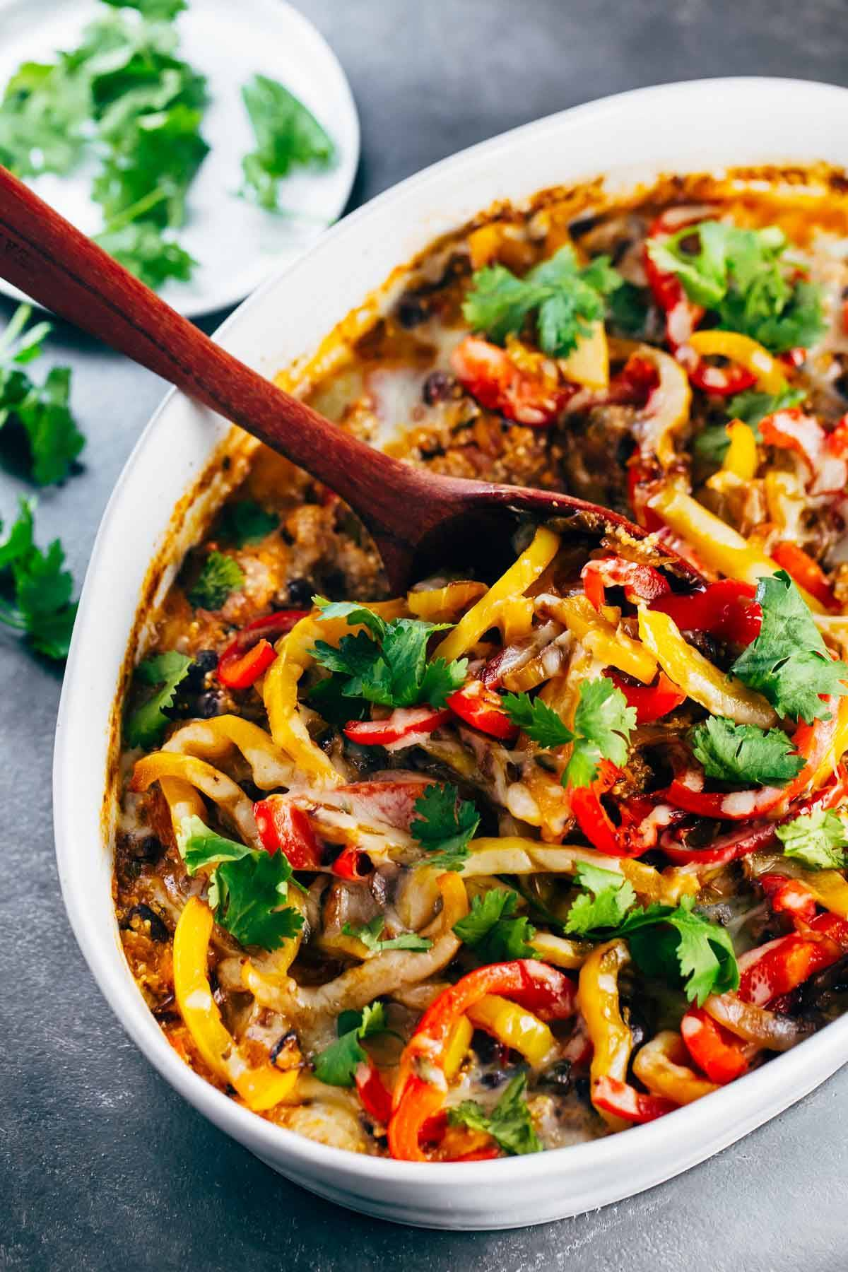 Mexican Chicken Quinoa Casserole in a baking dish with a wooden spoon.