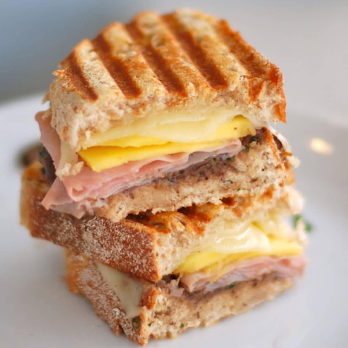 This nuevo cubano sandwich combines black bean cilantro puree, sliced mango, ham, and cheese layered between panini grilled bread. A twist on the Cuban! | pinchofyum.com