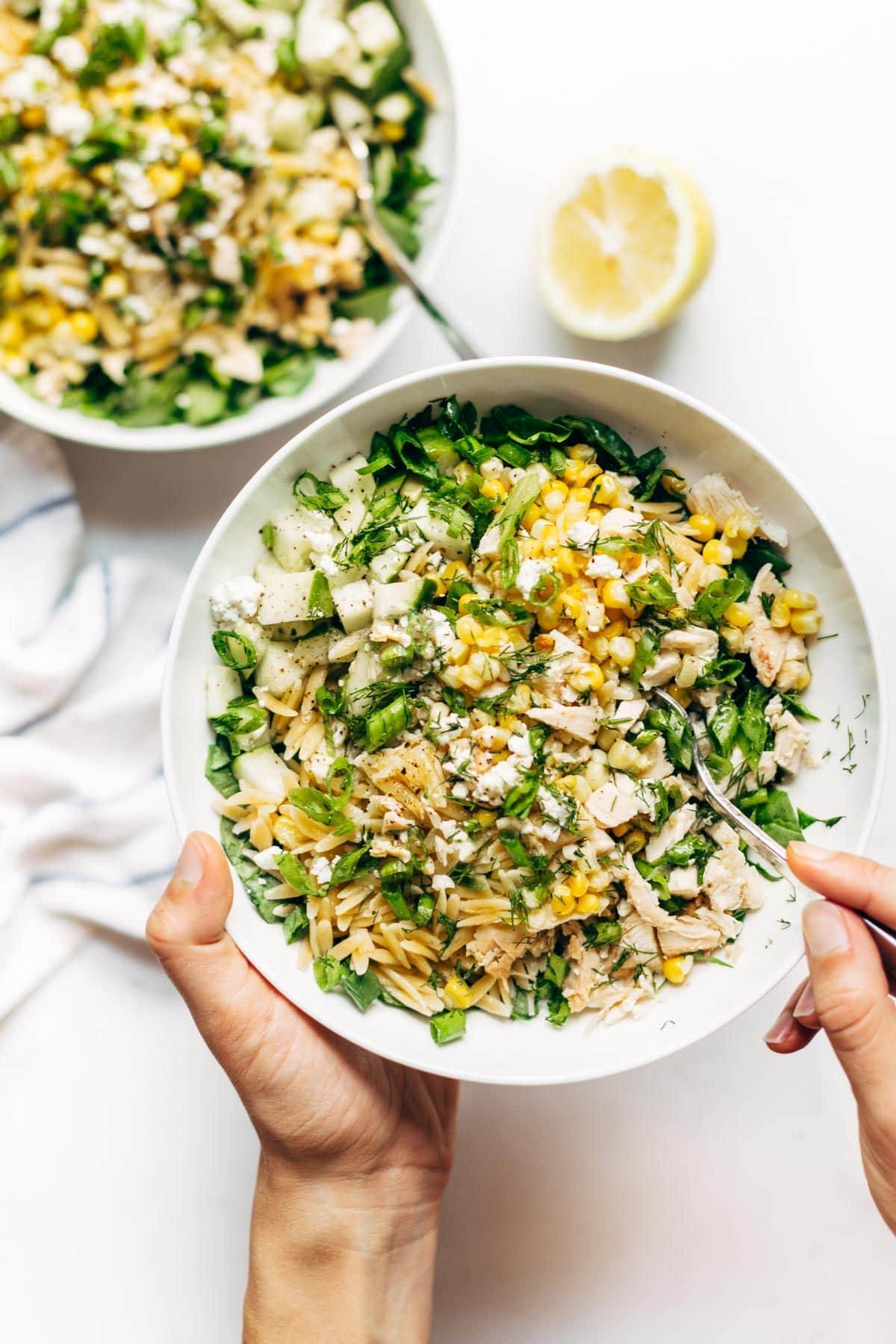 Hands holding Orzo Summer Salad with a fork.