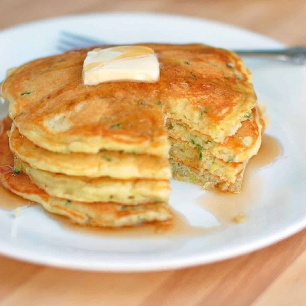 Stack of zucchini pancakes with butter and maple syrup on a white plate.