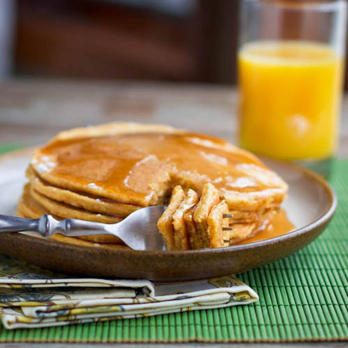 Stack of pancakes on a plate with a fork and a glass of orange juice.