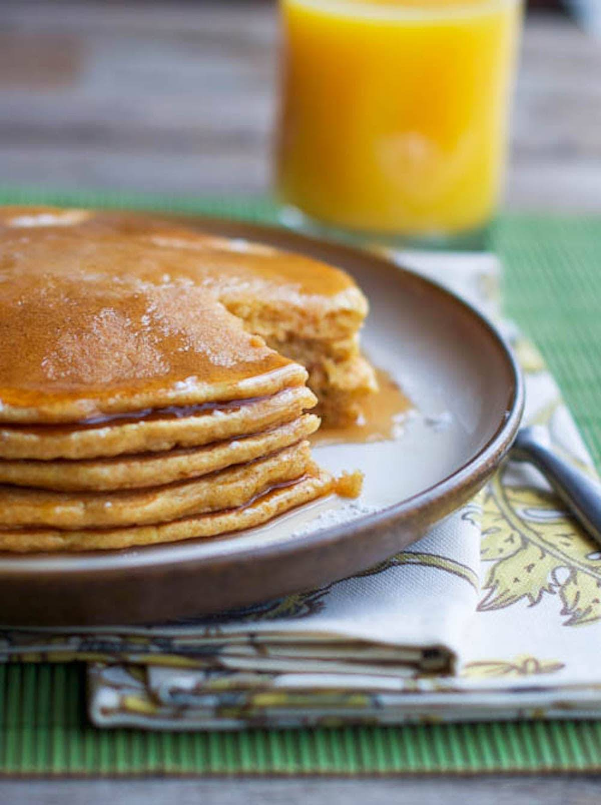 Pancakes with maple syrup and a glass of orange juice.