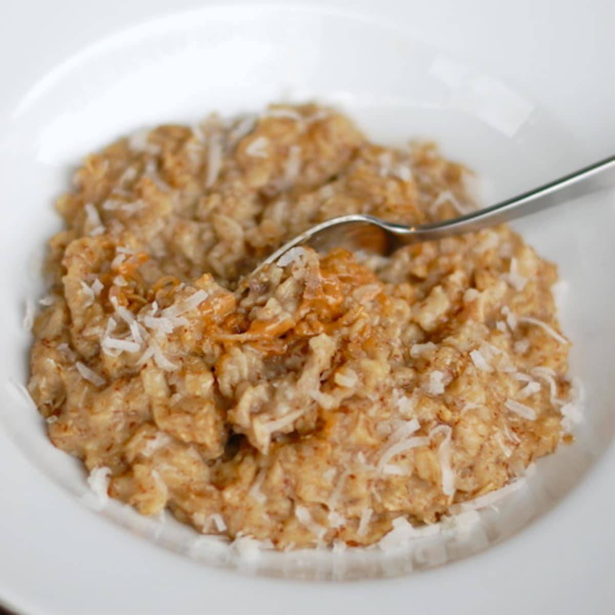Coconut peanut butter oatmeal with coconut shreds and a spoon.