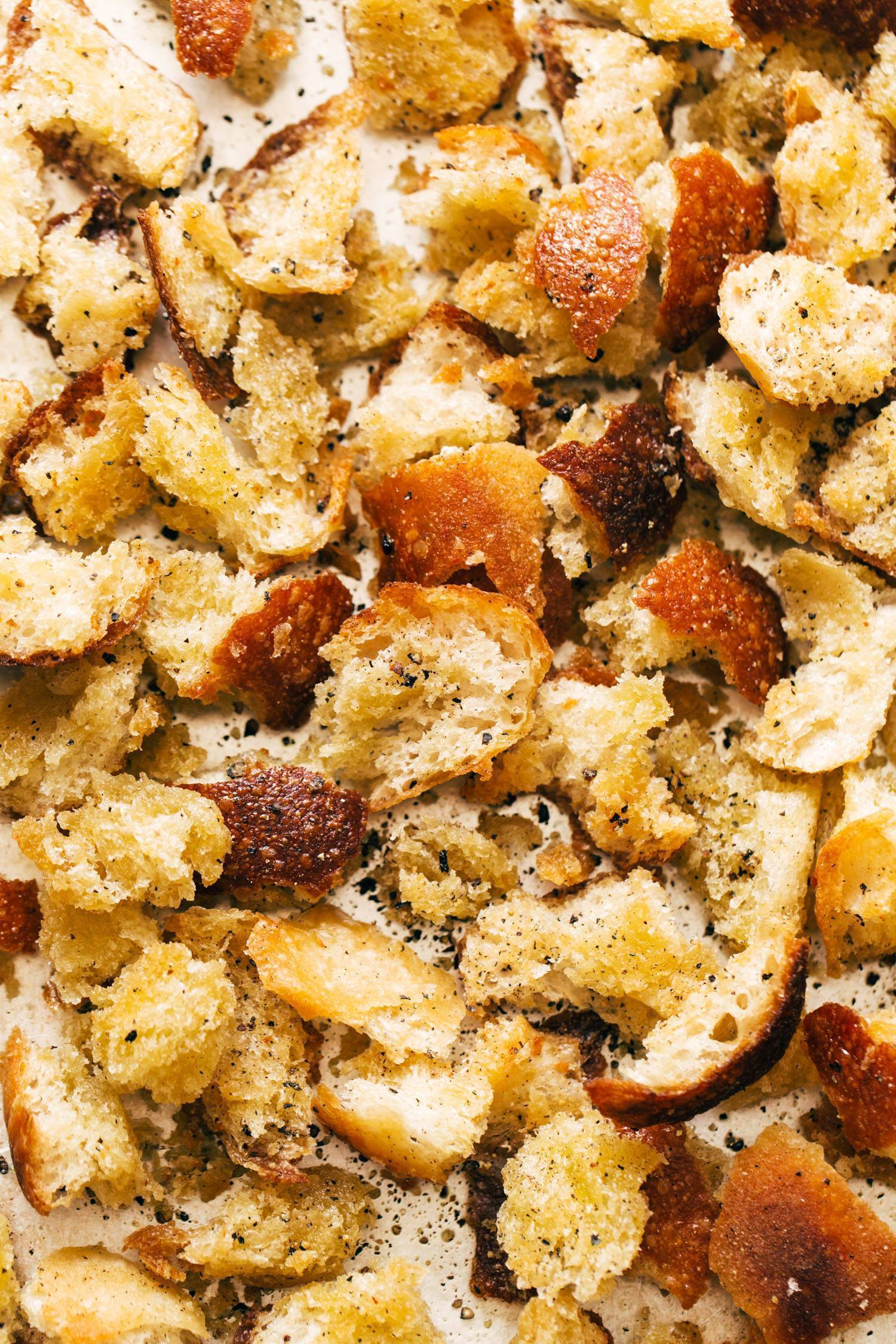 Peppery croutons on a sheet pan with olive oil.