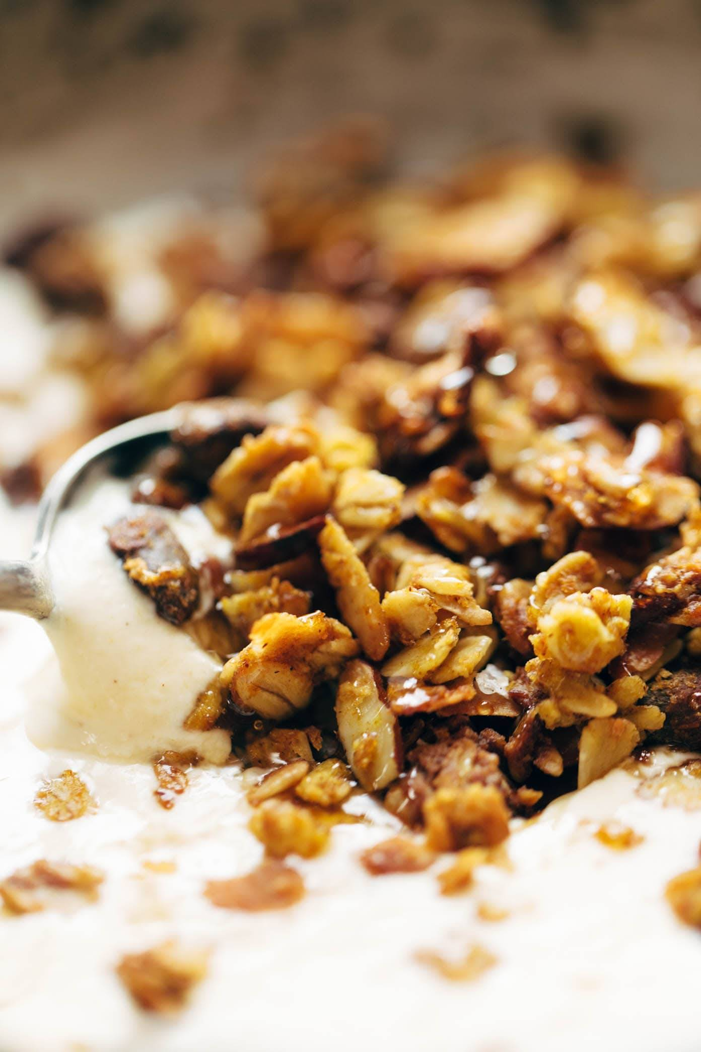 A close up photo of a spoon scooping pumpkin granola and yogurt.