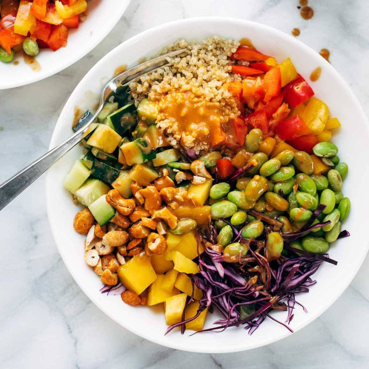 Quinoa salad with veggies in a bowl with a spoon.