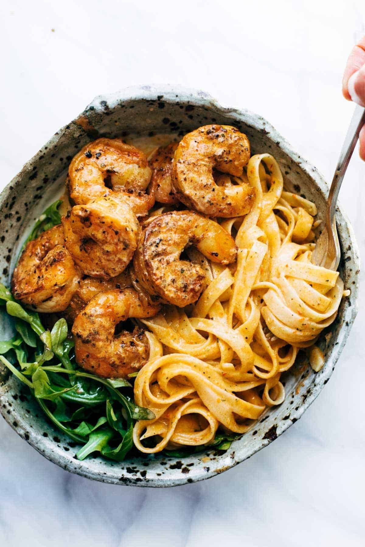 Red Pepper Fettuccine with Shrimp in a bowl with noodle twirl.