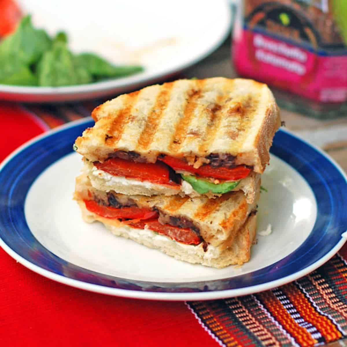 Red pepper and goat cheese panini with a layer of olive tapenade topped with roasted red pepper and soft, creamy goat cheese.