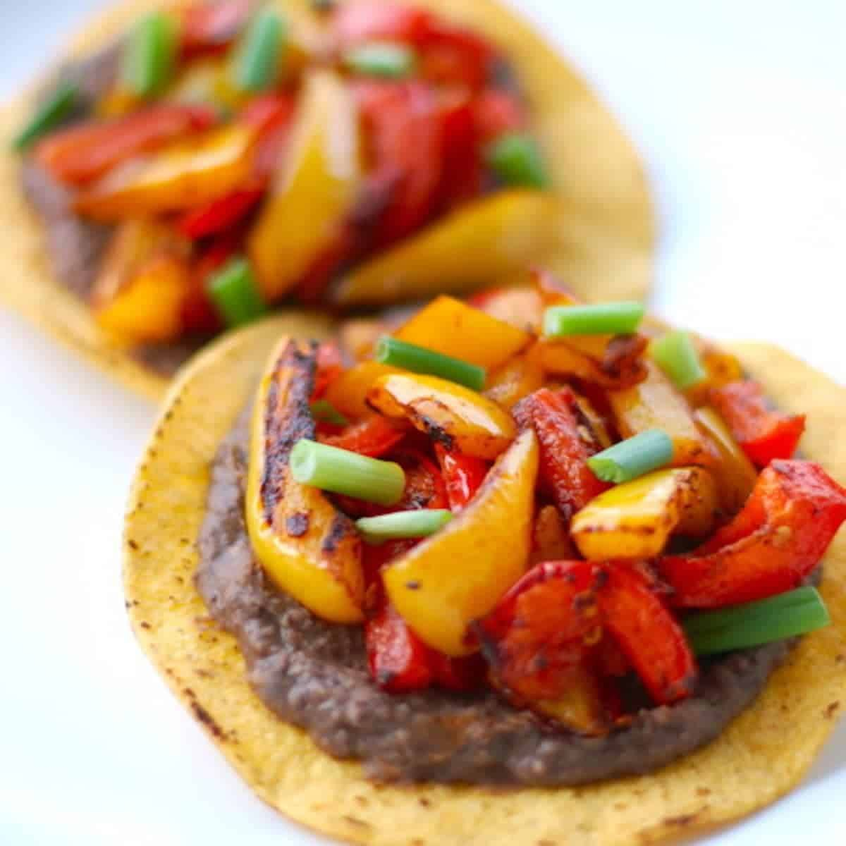 Two roasted bell pepper tostadas on tortillas.