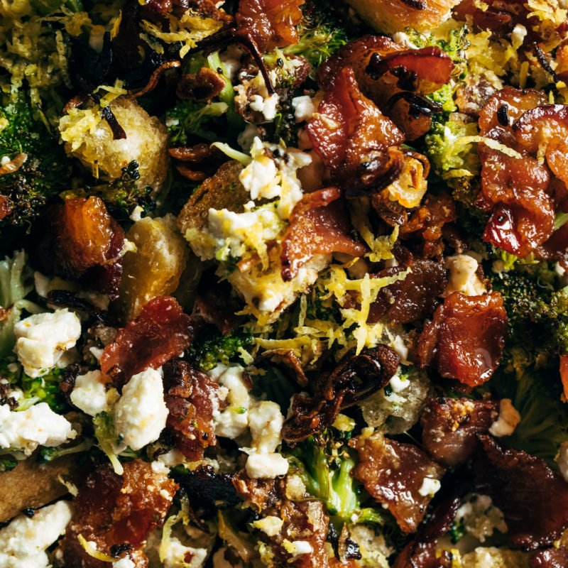 A broccoli salad with with bacon and croutons in it.