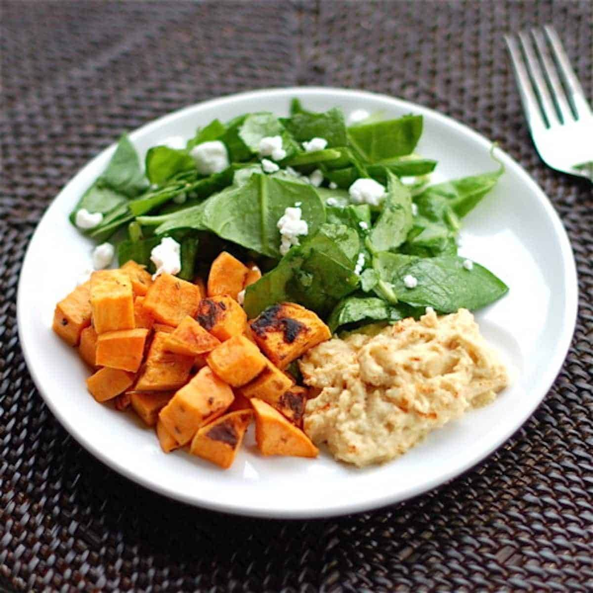 Roasted sweet potatoes with a side of hummus and a spinach salad on a white plate with a fork.