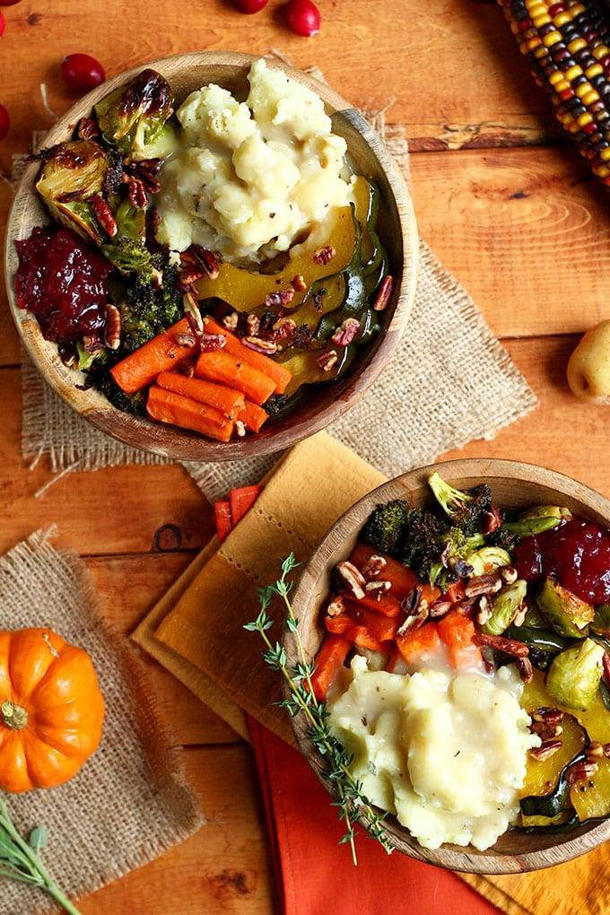 Two Roasted Vegan Thanksgiving Bowls in wooden bowls on a wooden table