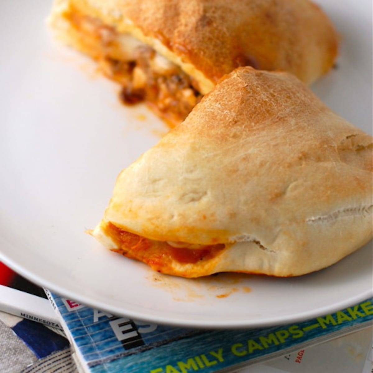 Sausage and mozzarella calzones on a white plate.