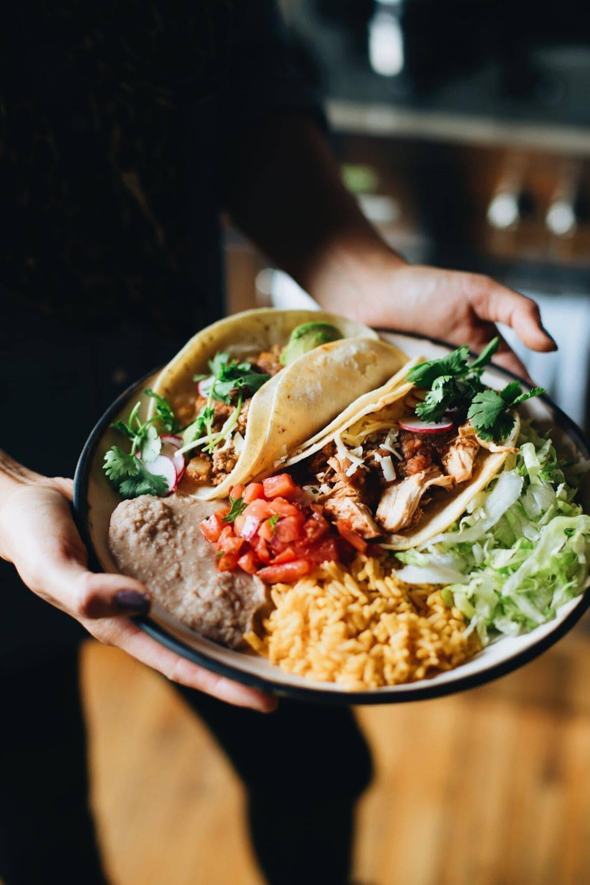Hands holding a plate of food.