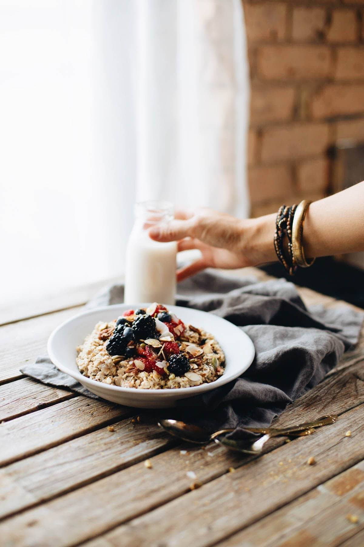 Hand grabbing a glass of milk next to a plate of granola with berries.
