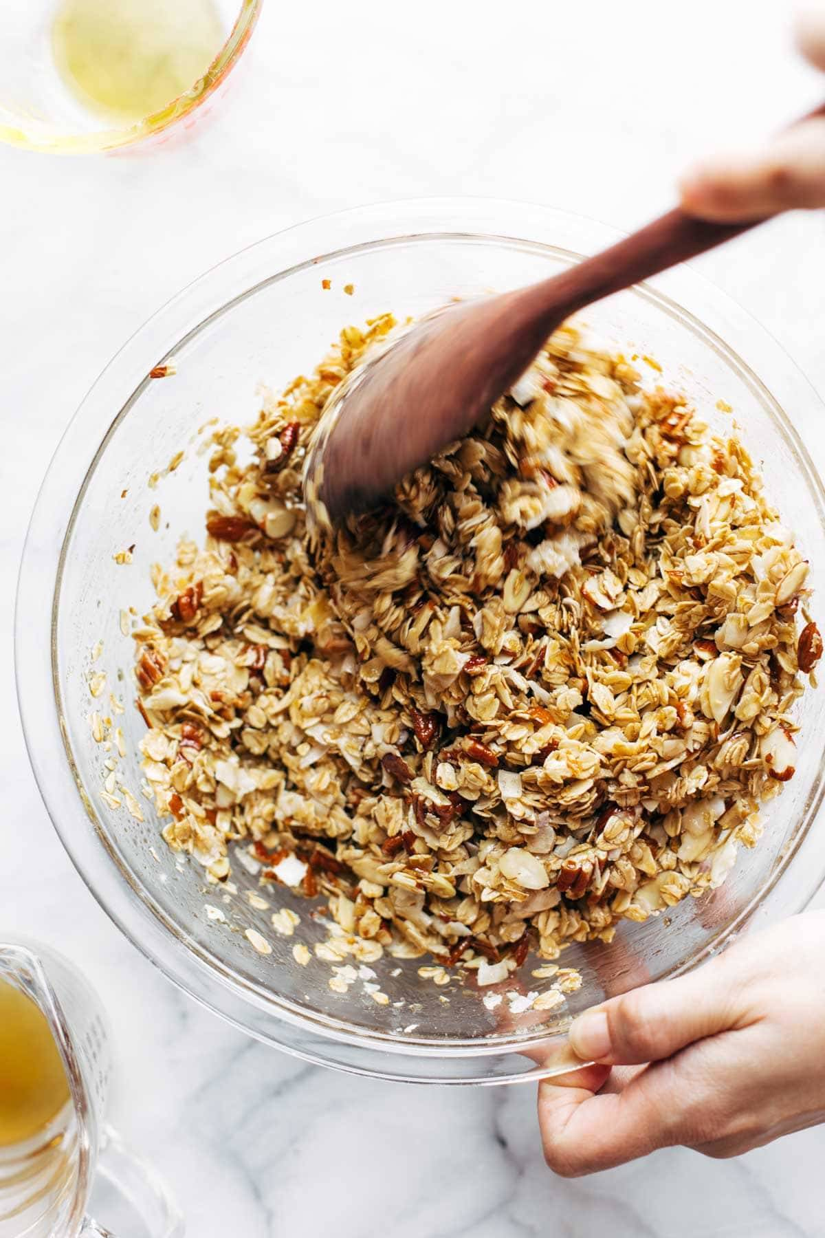 Mixing up granola ingredients with wooden spoon.