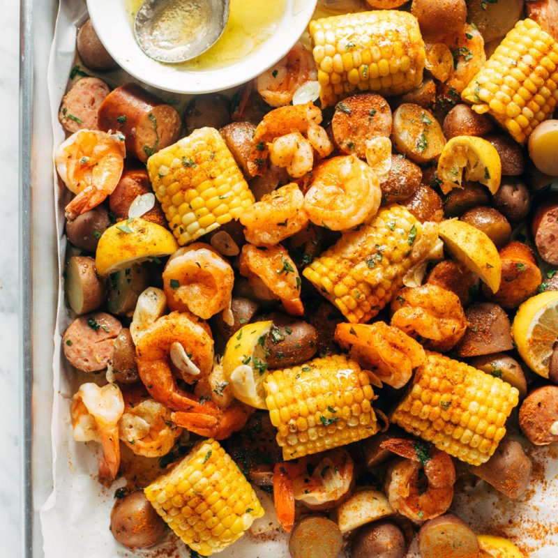 Shrimp, potato and corn mixture on a sheet pan with a side of melted butter in a bowl.